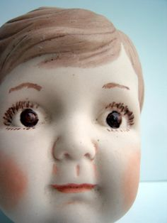 Handmade, Vintage Doll Parts: Boy Porcelain Doll Head Painted, Porcelain. From plushimi.  I don't think he's adorable at all - actually i think he's completely creepy!