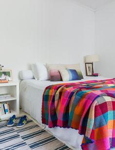 Quarto clean tem roupa de cama branca complementada por manta e almofadas coloridas.