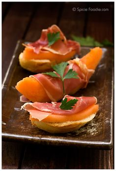 Melon con Jamon  cantaloupe or melon of choice  Jamon Serrano or any cured ham of your choice  sliced baguette or crusty bread, optional    In the photos you'll see that the melon and ham served two ways. Either wrap the jam around the melon slices or for smaller bites place small slices on top of baguette brushed with olive oil.