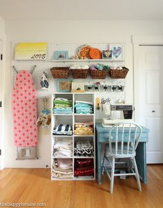 Wall in craft room for cubes holding material, sewing table/chair, ironing board, sewing machine. Peg board holds quilting ruler & mat. Baskets holding fabric.
