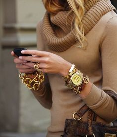 baggy sweater with chunky gold bracelets.