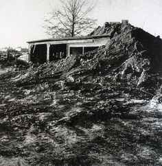 "Robert Smithson: Partially Buried Wood Shed, 1970. Kent state Campus. Image from Field Trips: Bernd and Hilla Becher / Robert Smithson. Museu Serralves, Porto 2001. Alan Bois 1997: ""Partially Buried Woodshed is a 'nonmonument' to the process Smithson calls 'de-architecturization': a dump truck poured earth onto the roof of an old woodshed to the point where its ridge beam cracked. Architecture is the material, and entropy is the instrument."""