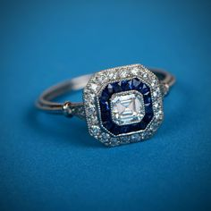 A lovely double halo Asscher cut engagement ring adorned with a halo of diamonds and sapphires.