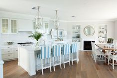 Beach kitchen with white cabinets topped with Carrara Marble counters and a white subway tiled backsplash. The angled kitchen island with sink is lined with white and blue striped slipcovered counter stools below a pair of Hundi lanterns. A white buffet flanks the kitchen cabinets topped with a pair of glass table lamps in front of a pair of framed abstracts.