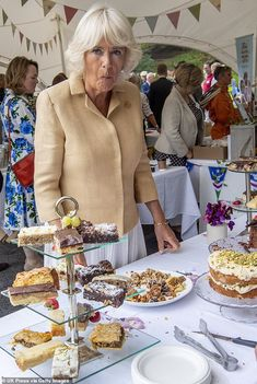 Enjoying a bite: Camilla was caught enjoying a bit of cake at the dessert table after a bu...