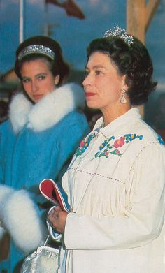 Queen Elizabeth and Princess Anne, mother and daughter. I can't read the look on Princess Anne's face as she stares at her mother. Is it it pride,  jealousy, contempt, or hate, lol? The Queen looks like she 's gloating over something. Maybe that's the reason for Princess Anne's look.