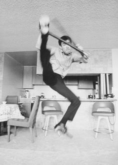 Bruce Lee performing a high kick with a three Section Staff