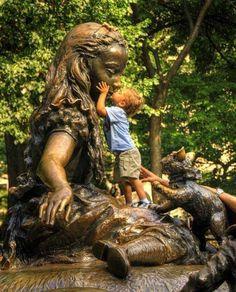 niño dandole un beso a la estatua