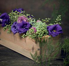 Caixas de vinho, flores e suculentas rendem um ótimo centro de mesa