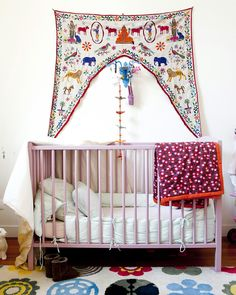 This baby nursery is decorated with a bohemian embroidered wall tapestry for a world-traveler feel.
