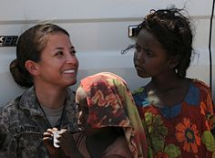 """U.S. Army Spc. Tiffany Larriba, team member from Civil Affairs Team 4902, 490th Civil Affairs Battalion, smiles at a child from the village of Karabti San, Djibouti, January 3. Children from the village gathered later that evening for Larriba's """"Soldier in the Classroom"""" program where she taught them basic English. U.S. Air Force photo by Senior Airman Jarad A. Denton"""
