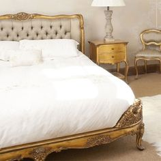 love this... the tufted headboard with the white linens and the gold accents