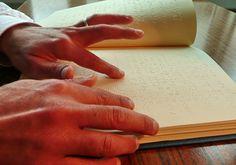 Mains d'une personne aveugle occupée à lire un document en braille.