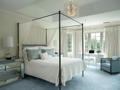 """Light and Lovely In this romantic baby blue and white bedroom, designer Sandra Oster paired glamorous design elements—mirrored bedside chests, a four-poster bed draped with diaphanous sheers, plush carpet—with unexpected touches. """"There's a strip of low-voltage pin spots on a wire over the desk,"""" Oster points out. """"And out of sight—but not to be missed—is the seed pearl edging on the waffle-weave fabric of the drapes."""""""