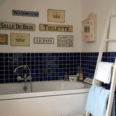 Quirky bathroom display  A display of vintage signs and notices adds personality to this small bathroom. Teaming the dark blue tiles with white grouting, walls and furniture lifts the deep shade, stopping it from making the bathroom seem smaller.