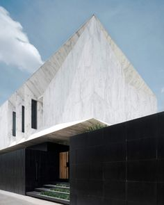 Wedge-shaped chunks are carved out of the marble-clad volume of this house in Bangkok, Thailand, which was designed by local studio Openbox Architects.