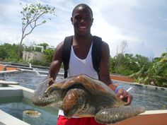 A Fresh Air child holds a sea turtle while visiting the Cayman Islands last summer, thanks to a partnership between the Department of Tourism, Cayman Airways, and The Fresh Air Fund.