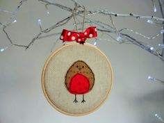 Adorable handmade hanging Christmas Robin embroidery hoop Christmas decoration. This handmade tree ornament is something a bit different from the shop bought baubles, and will be part of your Christmas decorations for years to come. The Christmas tree decoration is hand sewn and framed in an embroidery hoop, finished with ribbon. This cute little Christmas bird can be used as a Christmas tree decoration or hung as a piece of wall art for the festive period!  The embroidery hoop decoration…