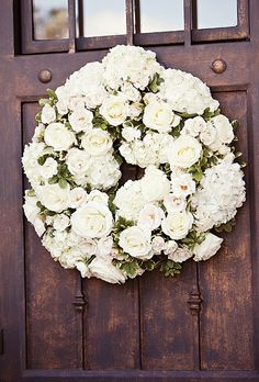 Brides: Lush White Floral Wreath. The wedding was held at Briscoe Manor, where a lush floral wreath adorned each chapel door.