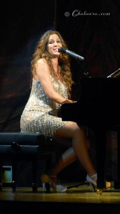 Maria Toledo sentada tocando el piano mientras canta