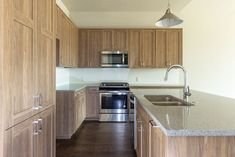 Warm, light brown tones in this transitional kitchen use EVRGRN Straan engineered wood with 5-piece doors