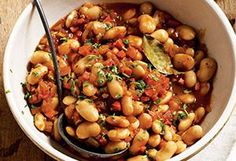 """Gigantes, or """"giant beans,"""" are large white beans similar to large limas, which are a good substitute. In this recipe, the beans are cooked Greek-style in a flavorful tomato sauce with vegetables and finished with tangy feta cheese. Serve the beans as they are or use them as a topping for cooked pasta."""