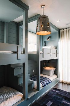 A gray built-in bunk bed staircase leads to side by side gray bunk beds with gray shiplap trim dressed in black and blue striped throw blankets illuminated by black sconces.