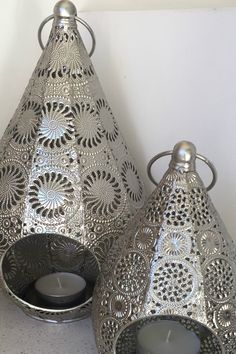 BEAUTIFUL SET OF MOROCCAN TEALIGHT CANDLE HOLDERS. AU $51.95 Pretty Indoor/Outdoor Tealight Candle Holder. Display indoors any room to add to the decor, or outside hanging or on a bench. Beautiful Silver Metal design. Elegant. Fits Small or Large tealight candles. Will include some taillight candles in the sale 2 Large and 2 Small.  1 is 32cm high, 16cm wide. 1 is 23cm high, 12cm wide.