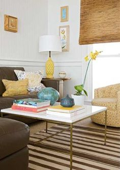 Brown Couch, walls, yellow lamp white table, stripe rug