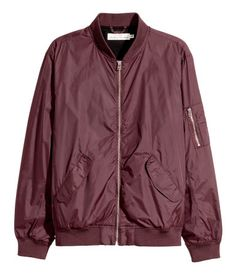 Plum. Nylon bomber jacket with a stand-up collar and front zip. Side pockets with flap, sleeve pocket with zip, and one inner pocket. Ribbing at cuffs and