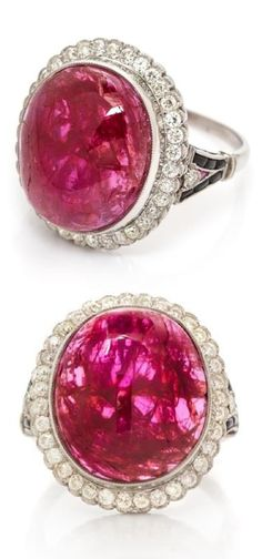 An Art Deco Platinum, Ruby, Diamond and Onyx Ring. Containing one oval cabochon cut ruby measuring approximately 16.80 x 14.50 x 5.00 mm, 37 old European cut diamonds weighing approximately 0.74 carat total, two triangular buff top rubies, and 12 calibré cut buff top onyx, openwork gallery and shoulders with scrollwork accents. #ArtDeco #ring