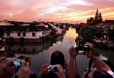Visitors take photos of sunset glow in Wuzhen, an ancient town in Tongxiang City, east China's Zhejiang Province, July 18, 2009. (Xinhua/Wang Song)