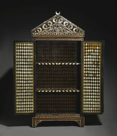 Interior  An Ottoman tortoiseshell, mother-of-pearl and ivory-inlaid cabinet with cintamani design, Turkey, 17th century    of rectangular form on bracket feet with hinged, lockable double doors opening to reveal a bone and ivory diamond lattice design and three shelves, surmounted by a decorative arched pediment set with crescent moon finial, inlaid throughout with ebony, ivory, bone, tortoiseshell and mother-of-pearl, the dominating design centred on the cintamani motif