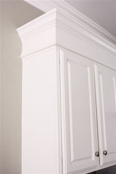 Kitchen DIY ~ Make kitchen cabinets look taller with custom molding ~ fake a custom look within a real persons budget. Accomplished with a nail gun, 1 x 4's, and thick decorative molding.