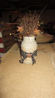 - handmade by Plain View Primitives - jar is painted a beige/tan color and is a textured paint to add more dimension to this arrangement - adorned with burlap, black gingham homespun, rust stars, and