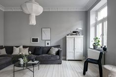 I like this connected dining and living room, each painted in a different shade of grey and decorated with grey, black and white furniture, accessories and green plants. Nordic Living Room, Living Room Decor, Living Spaces, Black And White Furniture, Lovely Apartments, Gravity Home, Beautiful Interior Design, Striped Wallpaper, White Rooms