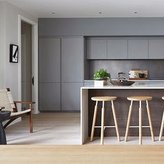 Grey kitchen, white worktops, wooden cladding on island