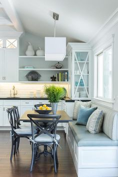 Lovely eat-in kitchen is filled with a built-in dining bench and window seat facing a French ...