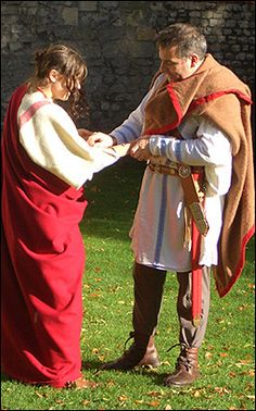 Dateline A.D. 211 Septimius Severus comes to York  The lady is keen to follow the fashions set by the wife of the Emperess Julia Domna, with curled hair and heavy make-up. She wears an under dress in linen, woollen overdress with integral clavi, and a palla. Her shoes are delicate boots with integral laces and pieced decoration.  The soldier wears a heavy pair of boots with integral laces, trousers with integral feet, and a linen tunic decorated with clavi. His military belt is secured to…