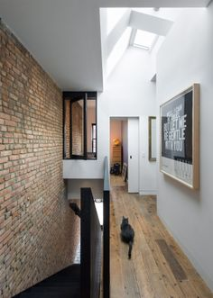 The skylight PULL tugs light from above to illuminate the brick party wall.