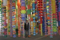 """Happy Happy Installation at LACMA """"Happy Happy"""" is created from wire-strung, plastic bins, bowls, cups and tubs that hang down like the remnants of a giant psychedelic shower curtain. The third outdoor """"Happy Happy"""" installation is an interactive project in which Choi has invited museum visitors to add their own plastic container sculptures to a section of LACMA's chain-link fence."""
