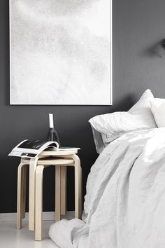 Bedroom with dark walls and stacked stools as a side table