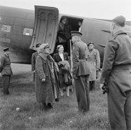 Ontvangst van Wilhelmina op vliegveld Gilze-Rijen bij de bevrijding van Nederland. ze wordt onder andere vergezeld door haar adjudanten E. Hazelhoff en P. Tazelaar