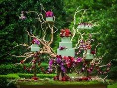 "For this New Orleans wedding with a ""Midsummer Nights Dream"" theme, Bee's Wedding and Floral Events used our cakes as a base for a floral design sculpture. We created several sizes of white chocolate lavender cake wrapped in moss green fondant. The cakes were suspended among manzanita branches and fresh floral leis."