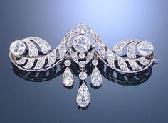 DIAMOND BROOCH, CIRCA 1915.  Designed as a stylised scroll embellished with millegrain-set circular- and single-cut diamonds, suspending at the centre three articulated pear-shaped drops similarly-set.