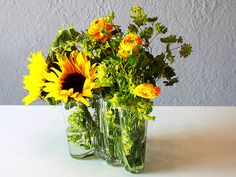 Bright yellow flowers make a cheery and low arrangement, perfect for the  dinner table.