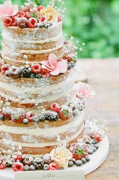 Beautiful naked cake dusted with powdered sugar, flowers & berries.