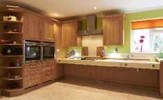 Large kitchen in natural oak with tall units to left of image, containing two integrated ovens and an end with open shelves for display stor...