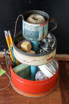 Metal 3-Tier Caddy made for utilitarian purposes with a rustic style. Repurposed from vintage metal tins it's perfect for organizing items on a desk, dresser, a shelf in your home or even used for entertaining. Caddy features three vintage tin canisters with a blue wooden center. And, the lids could become a stacked cake or snack server!