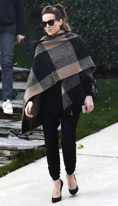 KATE BECKINSALE  looks extra classy wearing a large-check number as a poncho an all-black outfit, with cat-eye sunglasses and heels.